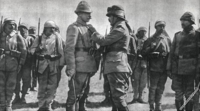 Mustafa Kemal, Harbiye Nazırı Enver Paşa'nın emrindeki subaylardan birine madalyasını takarken, tören alanında. (1915)